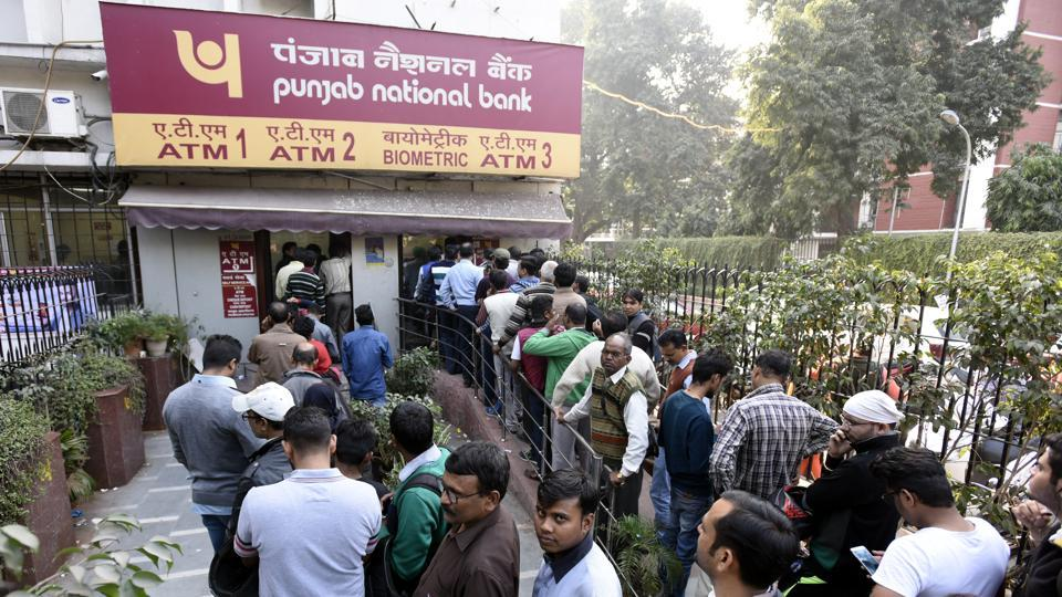 People stand in queue outside the PNB ATM to withdraw cash at Patel Chowk in New Delhi.