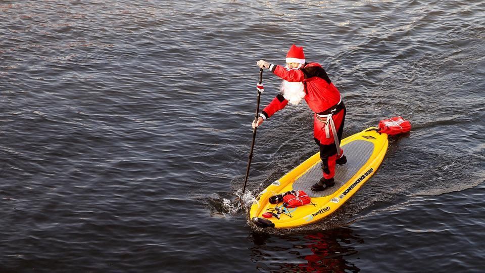 A man dressed as a Santa Claus (Samichlaus) crosses the Limmat river on his stand-up paddle in Zurich, Switzerland on December 4, 2016. (REUTERS)