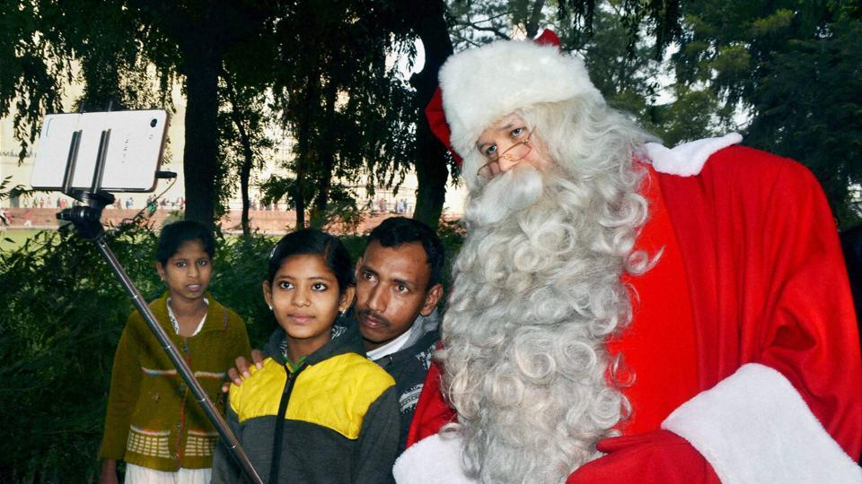 Santa Claus from Finland takes selfies with people in front of Taj Mahal during his visit to Agra on Tuesday. (PTI)