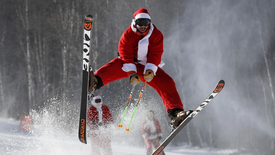 A skier dressed as Santa Claus catches some air during the annual Santa Sunday charity run on December 4, 2016 at the Sunday River Ski Resort in Newry, Maine.  (AP)