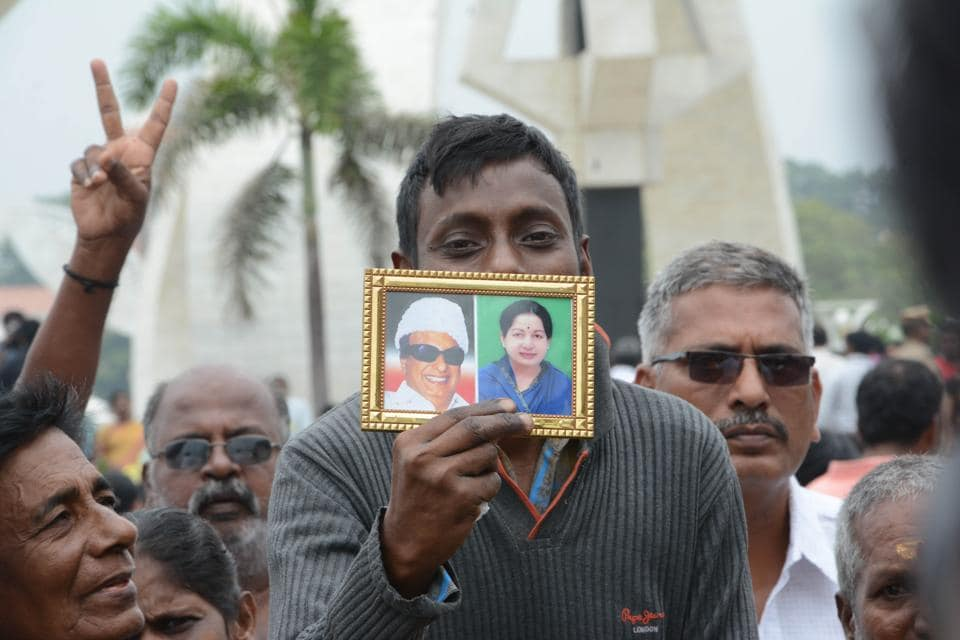 An AIADMK supporters show a photo of Jayalalithaa and her mentor MGR -- both of them died while in office --- in Chennai on December 07.
