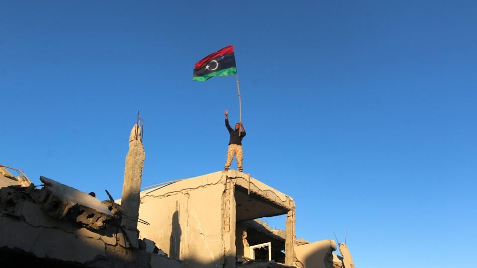 A fighter of Libyan forces allied with the U.N.-backed government waving a Libyan flag flashes victory sign as he stands atop the ruins of a house after forces finished clearing Ghiza Bahriya, the final district of the former Islamic State stronghold of Sirte, Libya.
