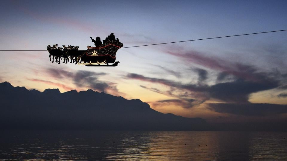 Santa Claus waves to the crowd from his flying sleigh drawn by reindeer over the Geneva Lake in front of the Swiss and French alps, on the first day of the 22nd edition of the Christmas Market in Montreux, Switzerland on December 6, 2016.  (AP)