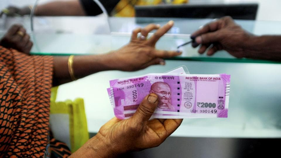 A woman displays her 2000 rupee notes as she has her finger inked with indelible ink after exchanging withdrawn 500 and 1000 rupee banknotes at a bank.