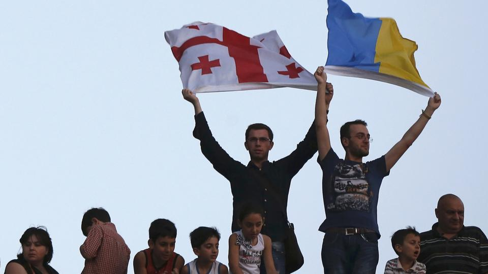 People hold up Georgian (L) and Ukrainian flags during celebrations after the signing of an association agreement with the European Union in Georgia in 2014.