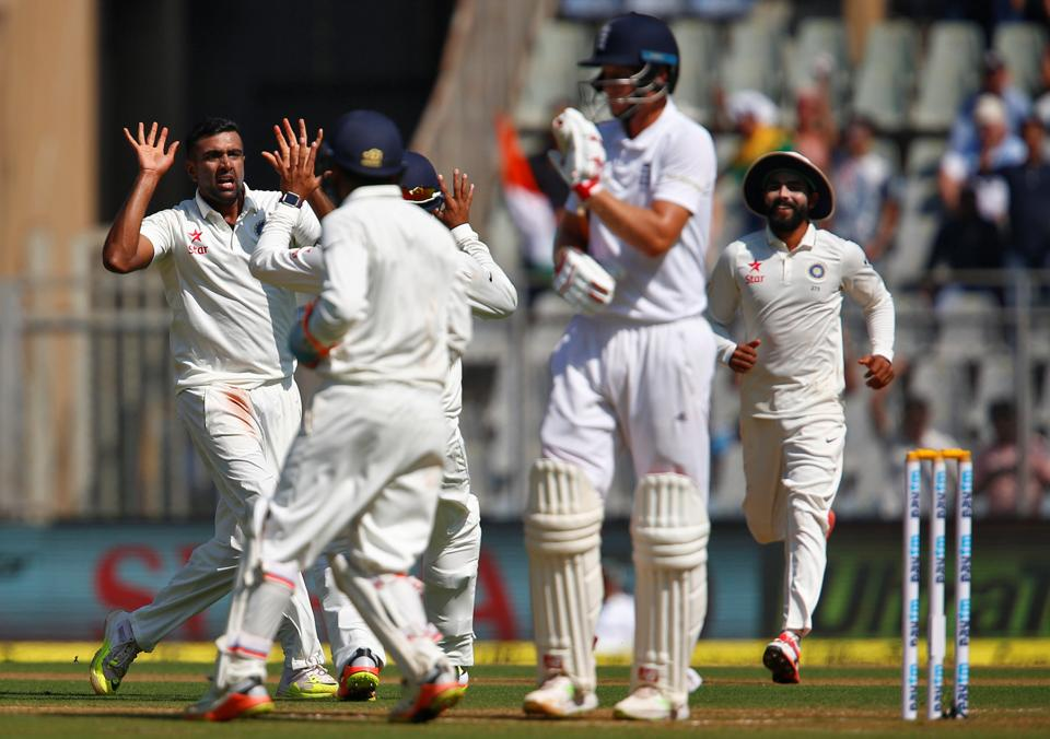 India's Ravichandran Ashwin (L) celebrates the wicket of England's Joe Root.
