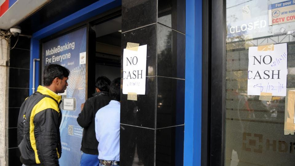 People stand outside an ATM displaying 'No Cash' notice, in Gurgaon.