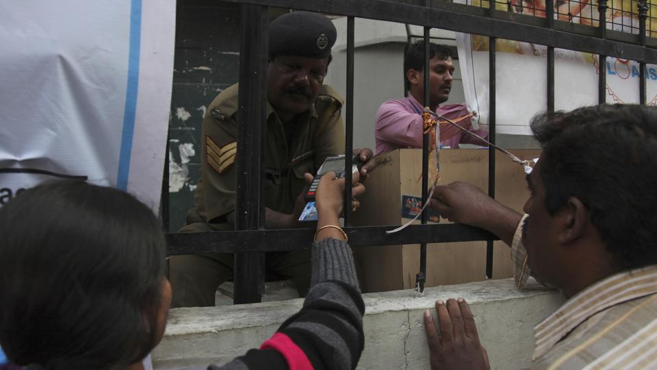 A woman enters her pin number after swiping her debit card to withdraw cash outside a State Bank of India branch in Hyderabad.