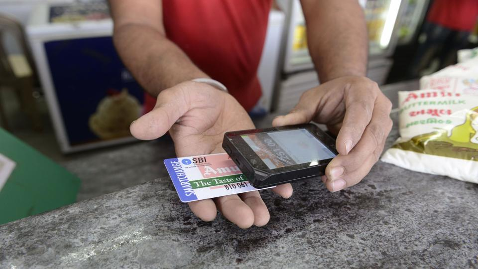 "A staff member scans a prepaid smart card at a Mother Dairy store, at Bhatt village on the outskirts of Ahmedabad. The government has decided to ""exempt services by an acquiring bank to any person in relation to settlement of an amount up to Rs 2,000 in a single transaction through credit, debit card or other payment card service""."