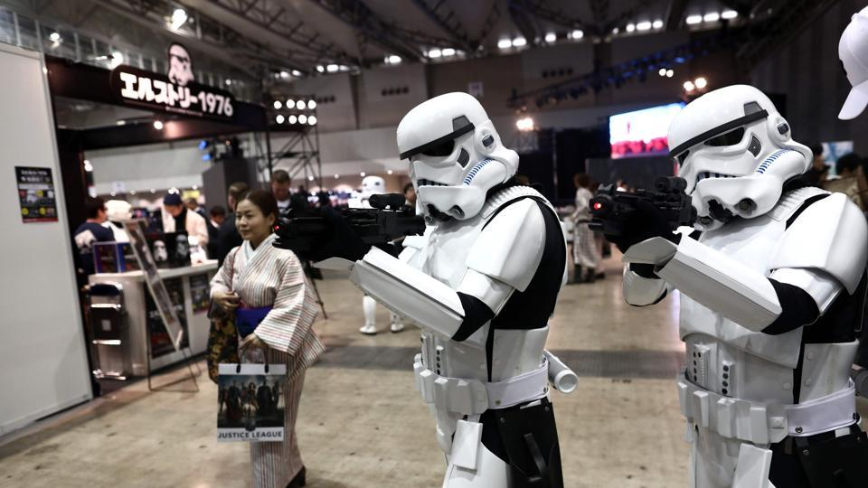 A Japanese woman in traditional Kimino walks past people wearing Star Wars characters' costumes during Tokyo Comic Con in Chiba in the suburb of Tokyo on December 2.