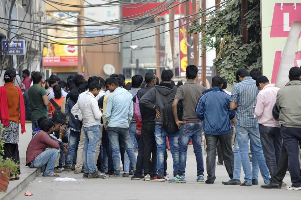 People stand in a long queues outside an ATM in Noida.