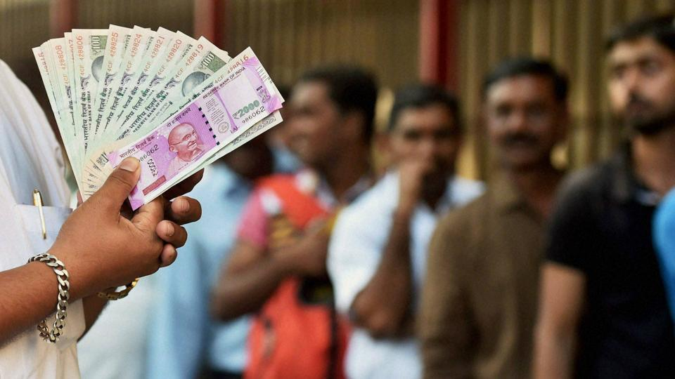 A man holds new Rs 2000 and Rs 100 notes outside the Reserve Bank of India, in Mumbai.