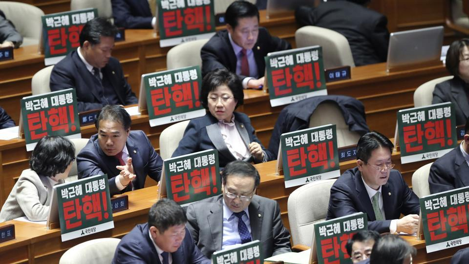 Lawmakers of opposition parties wait for the plenary session as they put placards reading