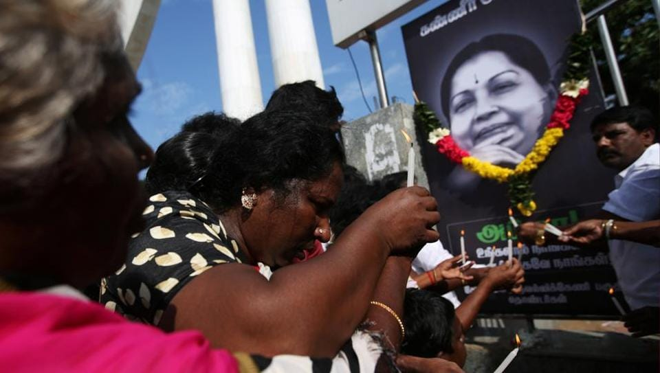 Supporters of Tamil Nadu chief minister J Jayalalithaa light candles in front of her picture as they pay homage outside Jayalalithaa's burial site in Chennai on December 7.