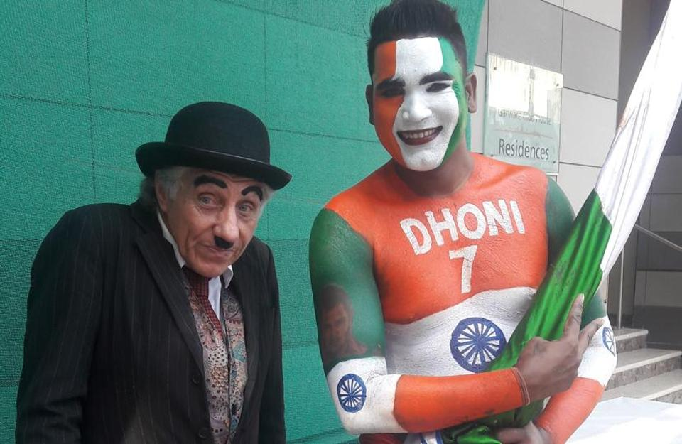 It is all balmy at the Wankhede as a member of the Barmy Army, England cricket team's fan club, dressed as Charlie Chaplin's iconic tramp character poses with a supporter of India's limited-overs skipper Mahendra Singh Dhoni.