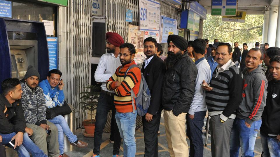 People waiting in a queue in front of a closed ATM in Sector 17, Chandigarh, on Thursday.