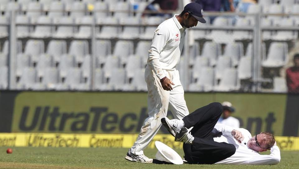Umpire Paul Reiffel falls after being hit by a ball during day 1 of the fourth Test between India and England held at Wankhede Stadium, Mumbai on Thursday.