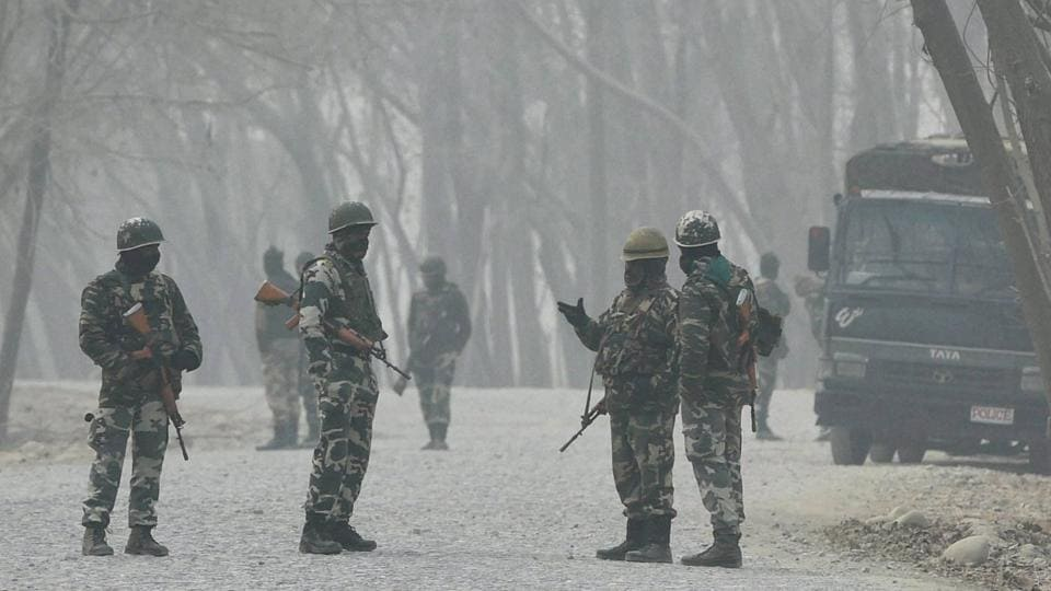 Security forces stand guard during a gunbattle between the army and militants at Arwani in Anantnag district of South Kashmir on Thursday.