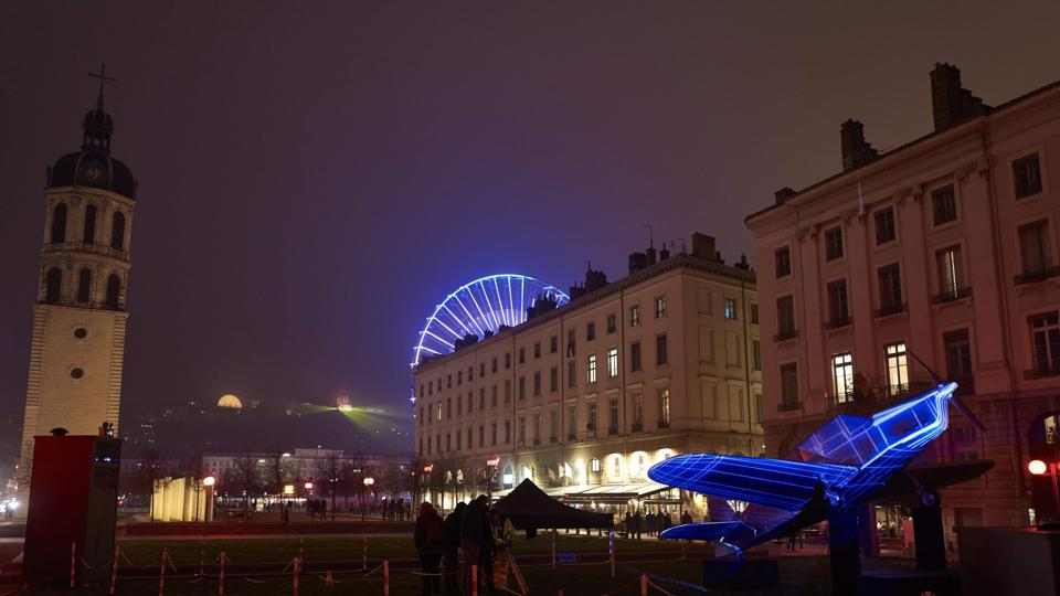The ferris wheel of Place Bellecour (rear), the bell tower (L) and an illuminated plane sculpture inspired by Vol de Nuit (Night Flight, Antoine de Saint-Exupery's 1931 novel) are pictured in downtown Lyon. (AFP)