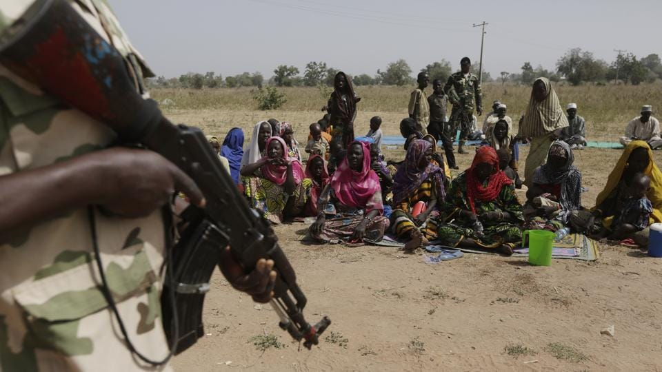 File photo of soldiers guarding people fleeing from Boko Haram's carnage in Nigeria.