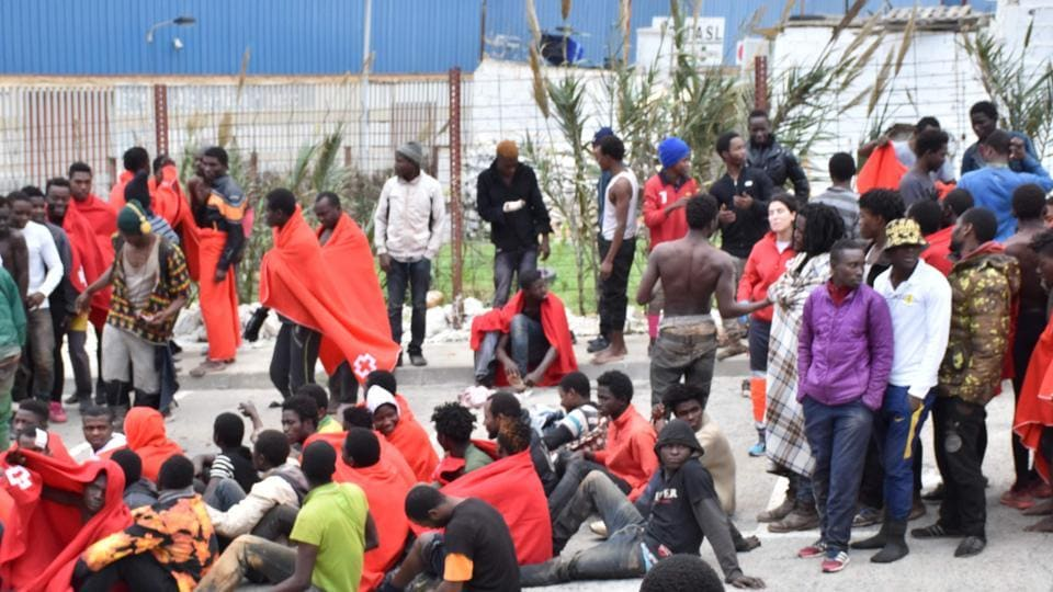 Migrants sit on the ground in El Tarajal, Ceuta, close to the boarder with Morocco on Fridat after being rounded up by police to be attended to by Red Cross personnel and taken to the Center for Temporary Stay of Immigrants (CETI) after nearly 400 migrants forced their way through a fence between Morocco and the tiny Spanish enclave of Ceuta, slightly injuring two police officers, authorities said.