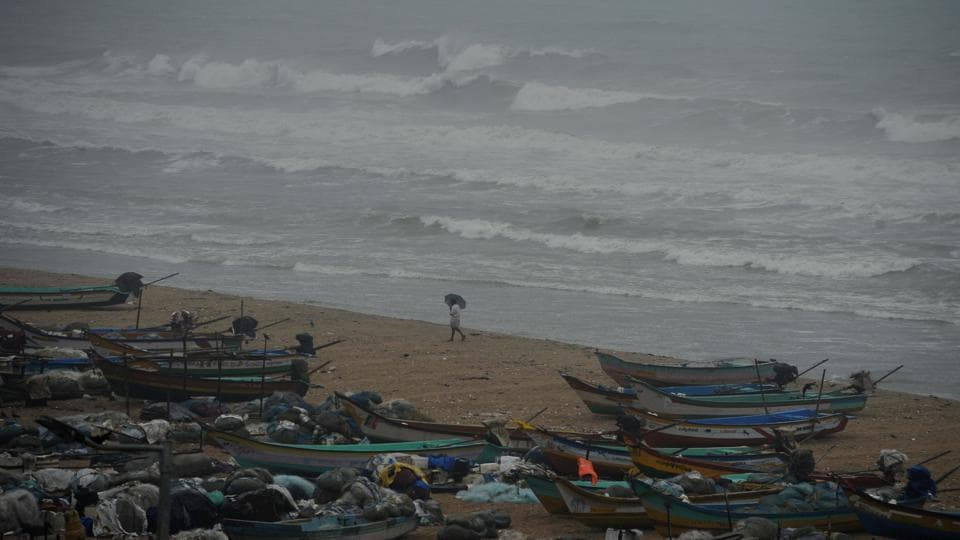 An Indian fisherman walks near boats as waves break on the cost of the Bay of Bengal in Chennai on Dec 1 when cyclone Nada was forecast to make landfall.