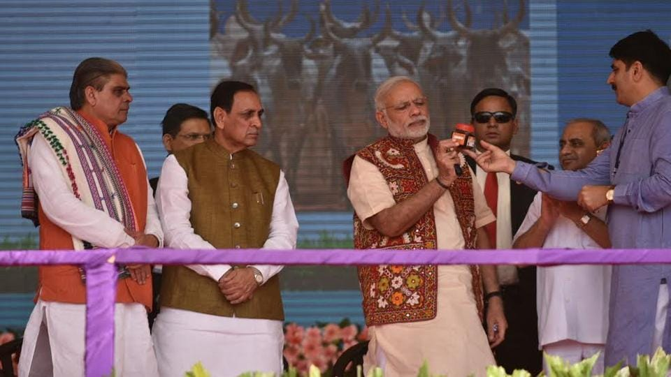 Prime Minister Narendra Modi holding a bottle of Banas Honey to mark its launch in Banaskantha district.