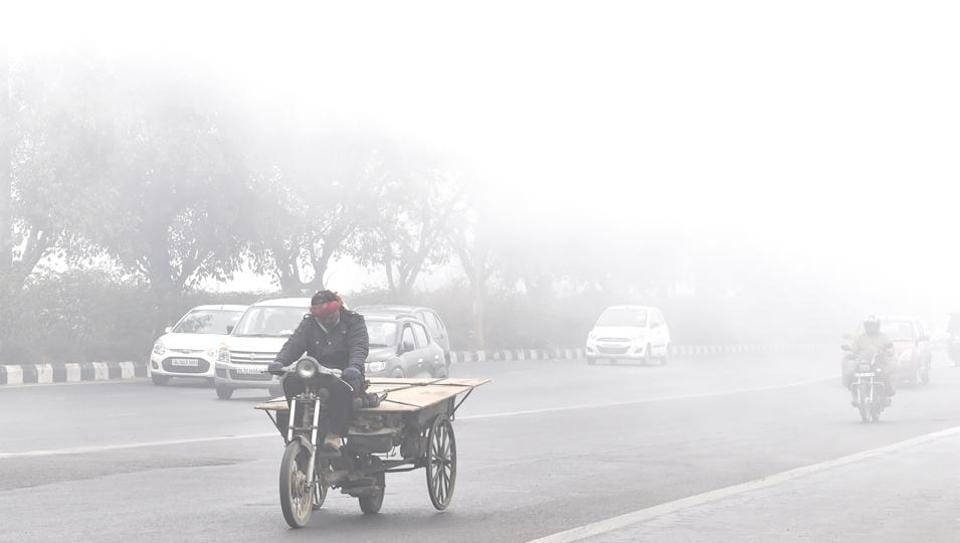 Commuters moving amidst dense fog in this winter season in New Delhi, India.