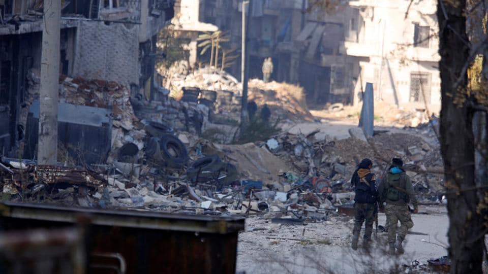 Forces loyal to Syria's President Bashar al-Assad walk past damaged buildings in a government held area of Aleppo, Syria December 9, 2016.