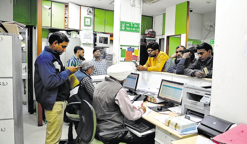 People wait at the Oriental Bank of Commerce in Sector 14 to withdraw cash.