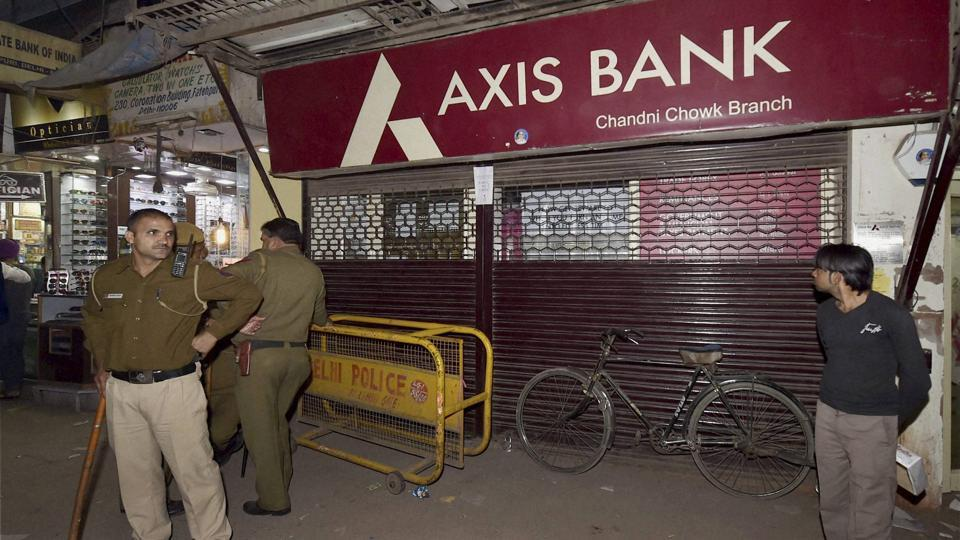 Police men guard outside an Axis Bank branch during a raid by Income Tax officials in the Chandni Chowk in New Delhi on Friday. The officials have found several fake accounts in the bank.