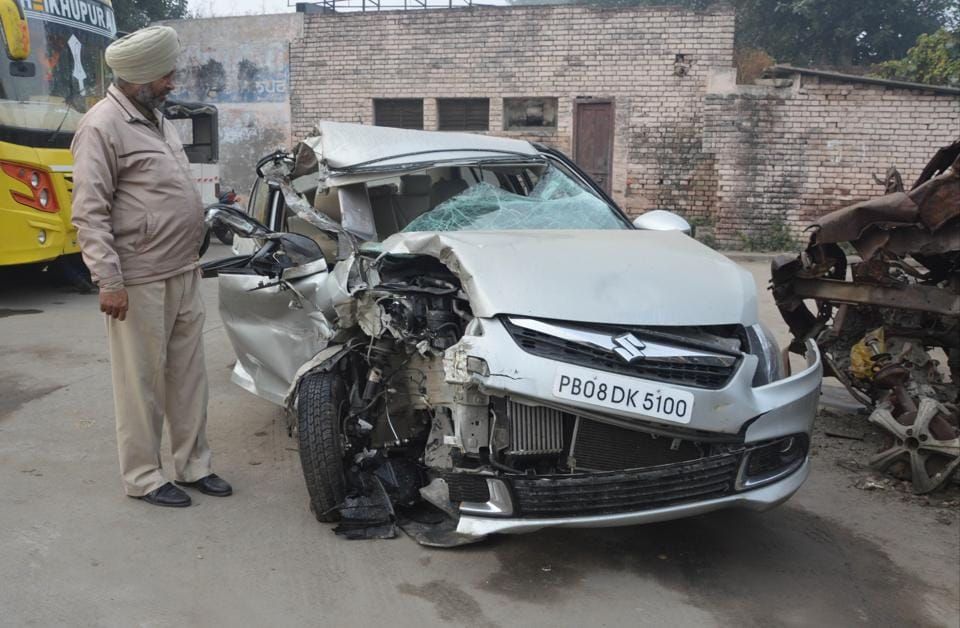 A policeman looking at the damaged car after the mishap in Jalandhar on Friday.