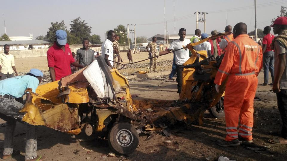 In this Saturday, October 29, 2016 file photo, People clear debris after an explosion in Maiduguri, Nigeria. Nigeria's army says two women suicide bombers blew themselves up Friday morning at a market in northeast Nigeria's Madagali town.