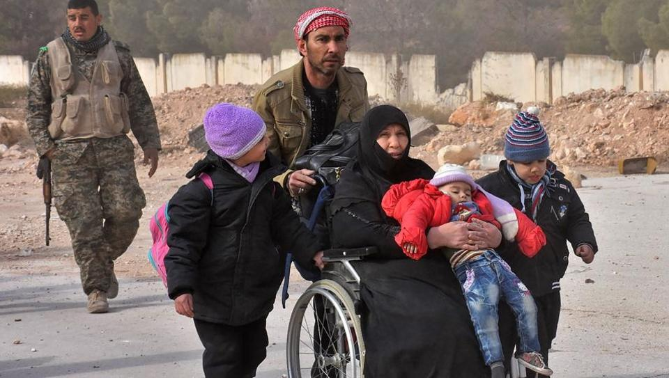 Members of Syrian government forces assist families, fleeing from various eastern districts of Aleppo and heading to government-controlled western Aleppo.