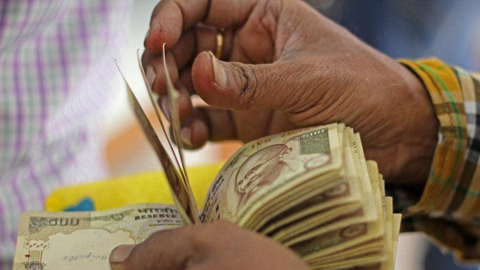 Mumbai, India - Nov. 21, 2016: A man counts old 500 and 1000 notes inside the bank at Vashi in Mumbai, India, on Monday, November 21, 2016. (Photo by Satyabrata Tripathy/ Hindustan Times)