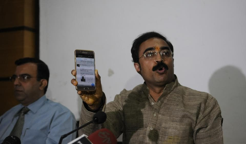Sanjay Masani shows Anand Rai's Twitter feed during a press conference in Bhopal.