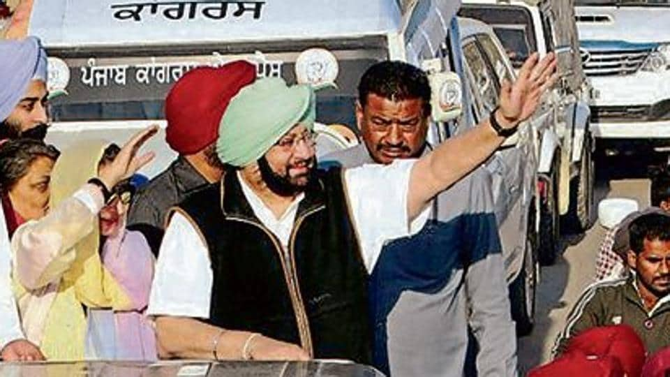 Punjab Congress chief Amarinder Singh and his wife, MLA Preneet Kaur, wave to supporters at a road show in Patiala.