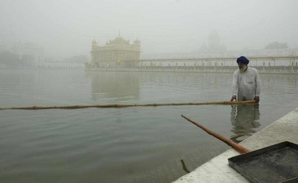 A worker cleans the holy sarovar (pond) at the Golden Temple in Amritsar on a foggy morning. (Gurpreet Singh/HT)