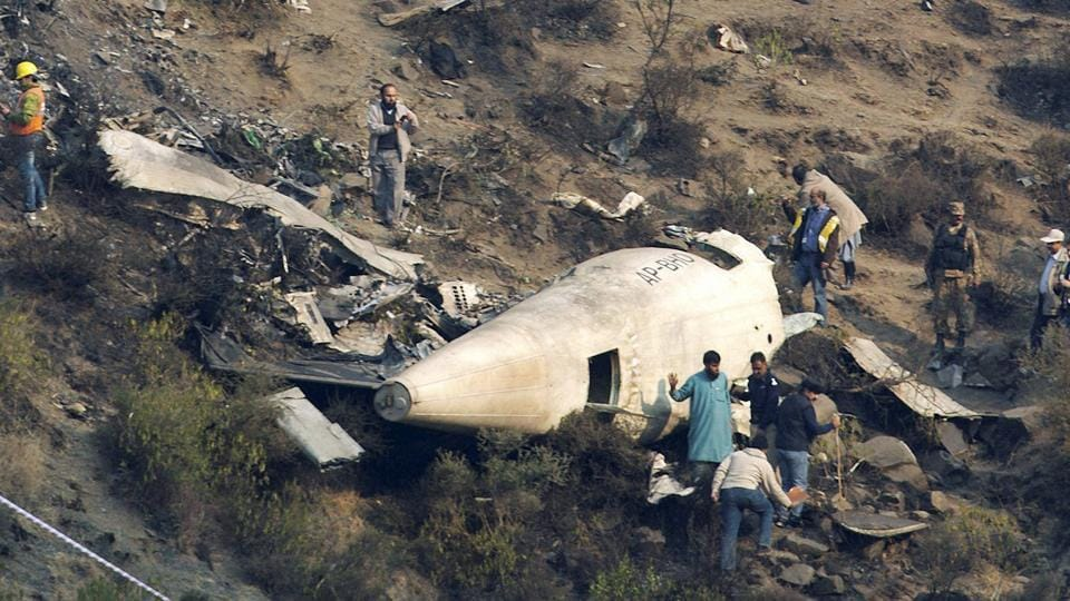 Pakistani investigators examine the wreckage of a passenger plane which crashed in the village of Gugh.