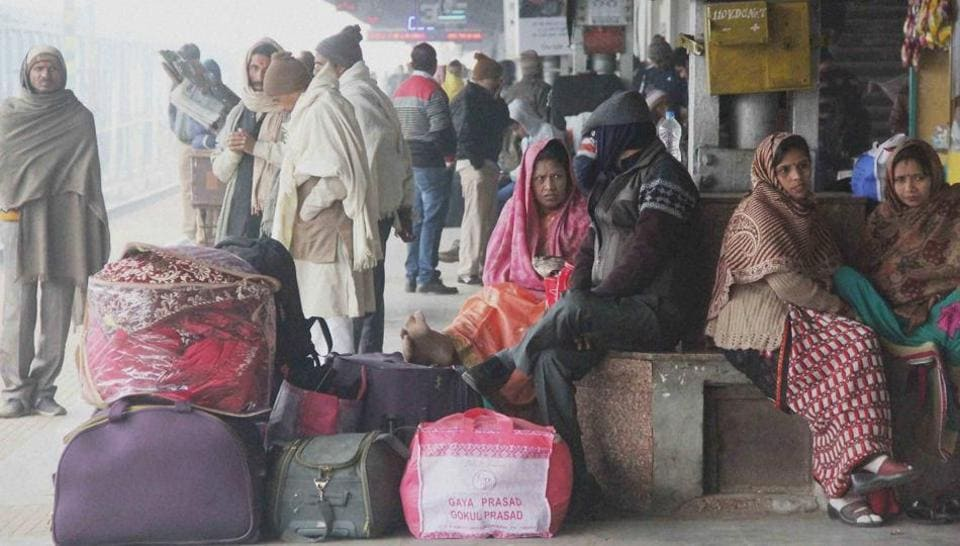 Stranded passengers wait for their trains as many were running late due to the fog, at Allahabad Railway Station on Sunday.