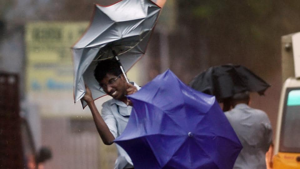 A man struggles to hold on to his umbrella as high speed winds accompanying cyclone Vardah whipped the southeastern coast on Monday.