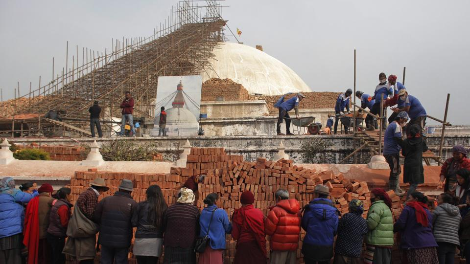 Nepalese people help in reconstruction of a monument damaged in the April, 2015 earthquake in Kathmandu.