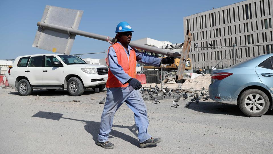 A migrant worker carries a pole at a construction site in the Qatari capital Doha. Ever since being chosen as the 2022 World Cup host, Qatar's labour laws have been internationally condemned and kafala has been at the heart of that criticism.
