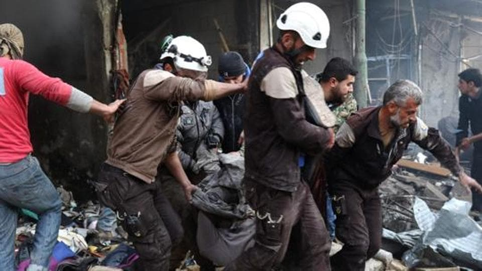 Syrian men and Civil Defence volunteers, also known as the White Helmets, evacuate a victim from a building following an air strike on the village of Maaret al-Numan.