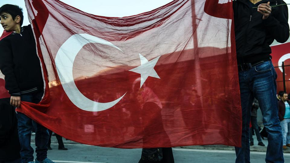 Youth hold a Turkish flag during a gathering outside the Vodafone Arena football stadium in Istanbul on December 11, 2016, a day after twin bombings near the home stadium of Besiktas football club.