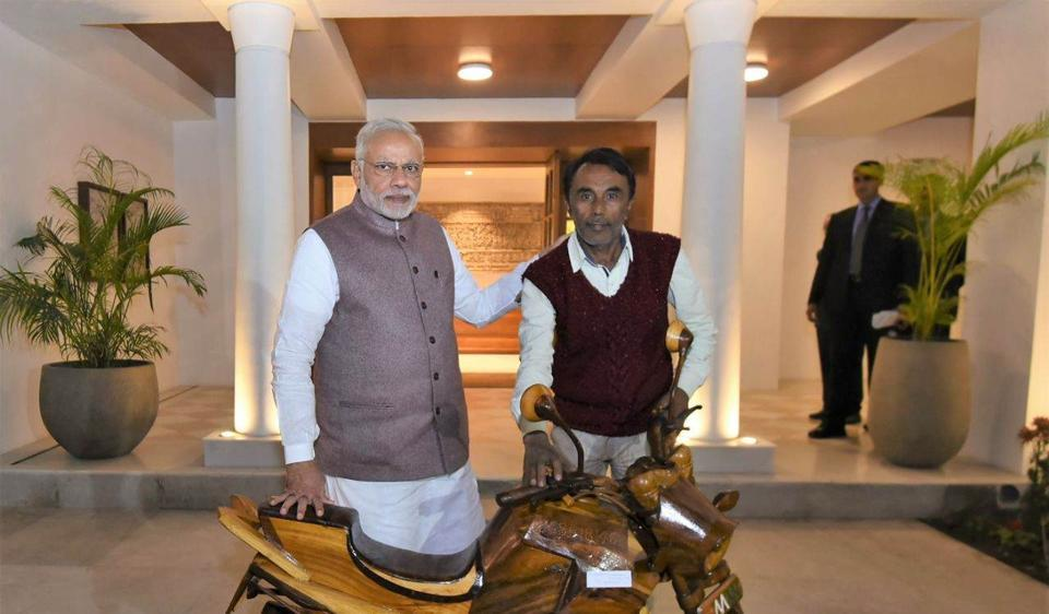 Buddhasen Vishwakarma (right) with PM Narendra Modi after gifting the wooden mobike in New Delhi recently.