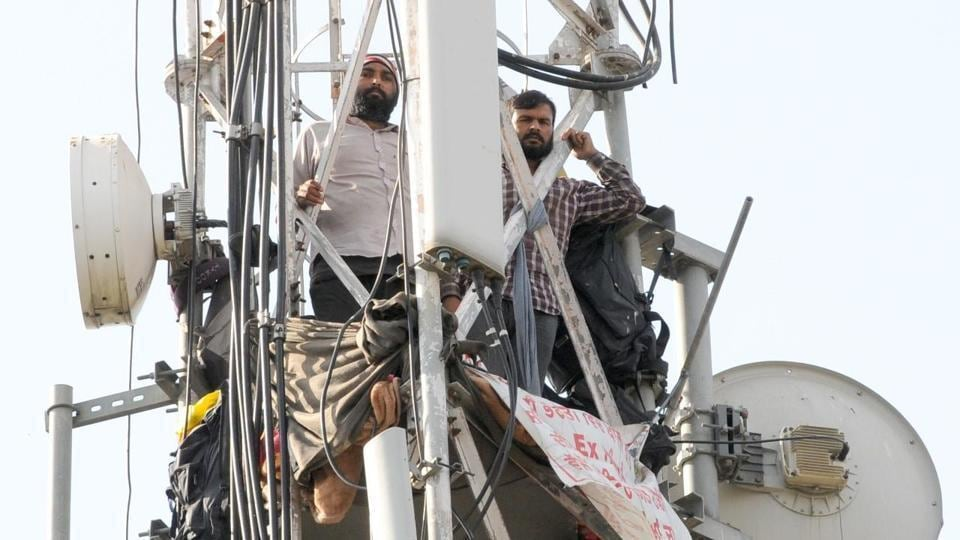 Deepak Kumar and Rakesh Kumar atop a mobile tower that they climbed on November 3, in Chandigarh. Rakesh has now come down.