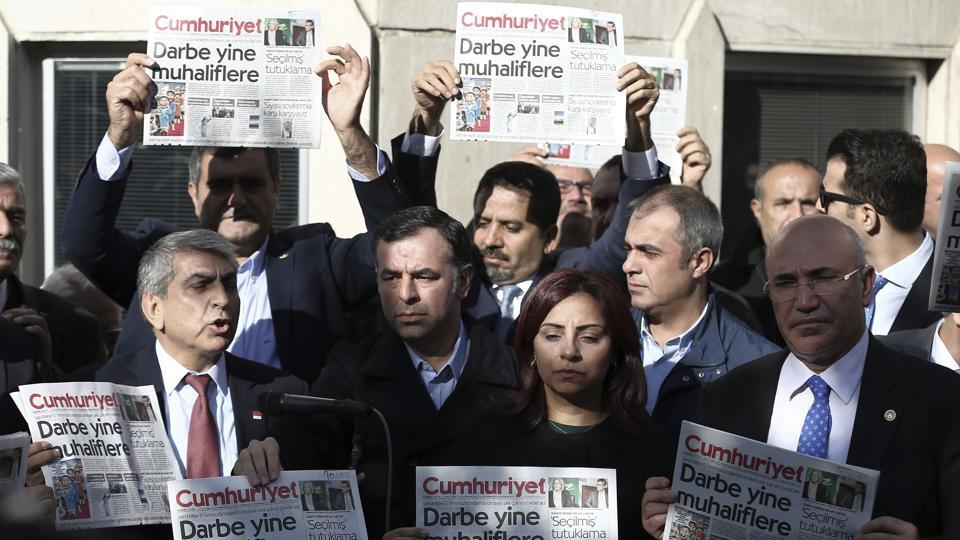 Journalists and lawmakers hold the latest copy of Cumhuriyet newspaper outside its Istanbul headquarters after the police detained its chief editor and two columnists in Turkey in October.