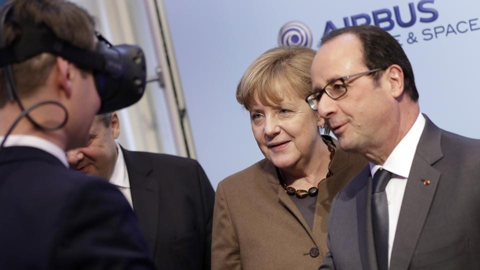 German Chancellor Angela Merkel, left, and French President Francois Hollande, right, talk to a man wearing virtual reality glasses during a German-French 'Digital Conference' in Berlin, Germany.