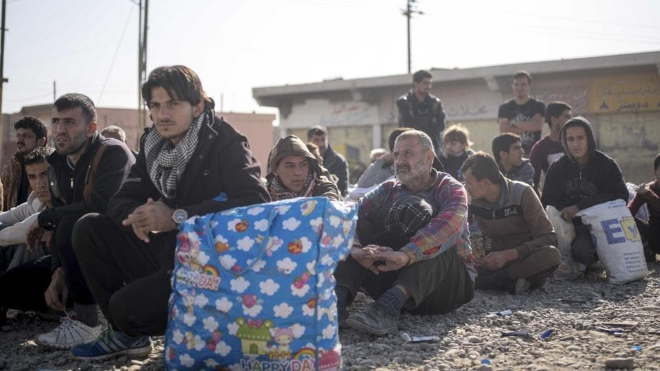 Iraqi men who have fled fighting between militants and Iraqi forces in Mosul are sequestered at a collection point in Gogjali, Iraq. During their rule of Mosul, the Islamic State group brutally purged whole sectors of the once multicultural city, targeting Kurds, Shia and Christians, hunting down former police and soldiers in their homes and hanging anyone caught with a mobile phone from lamp posts.